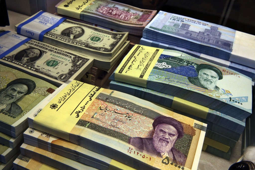FILE - In this April 4, 2015 file photo, Iranian and U.S. banknotes are on display at a currency exchange shop in downtown Tehran, Iran. Iran's curren...