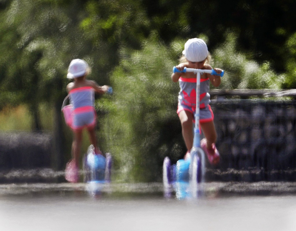 Two little girls ride their scooters through the shimmering heat on the tarmac of a former military airport in Frankfurt, Germany, on a hot Monday, Ju