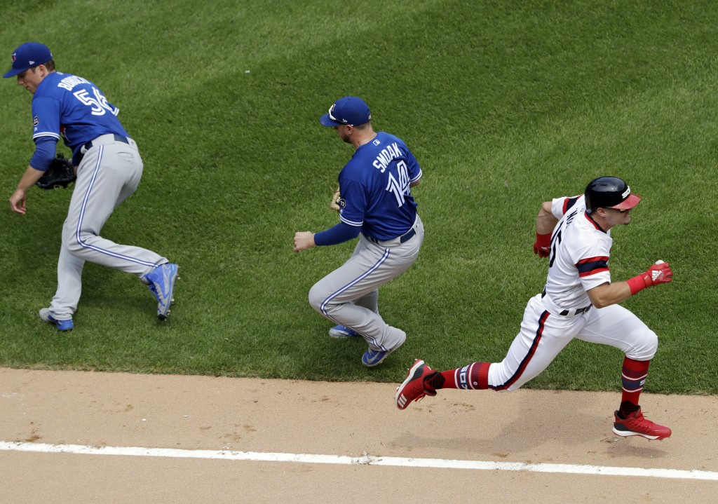 Chicago White Sox's Adam Engel, right, runs to first base after hitting a bunt-single as Toronto Blue Jays starting pitcher Ryan Borucki, left, and fi...