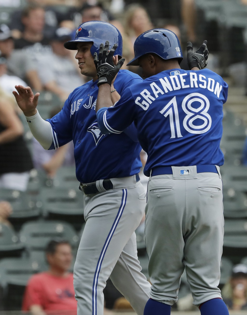 Toronto Blue Jays' Aledmys Diaz, left, celebrates with Curtis Granderson after scoring on a two-run double by Brandon Drury during the ninth inning of...
