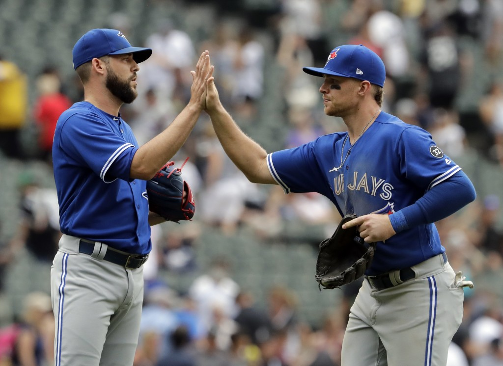 Toronto Blue Jays' Brandon Drury, right, celebrates with relief pitcher Ryan Tepera after they defeated the Chicago White Sox in a baseball game Sunda...