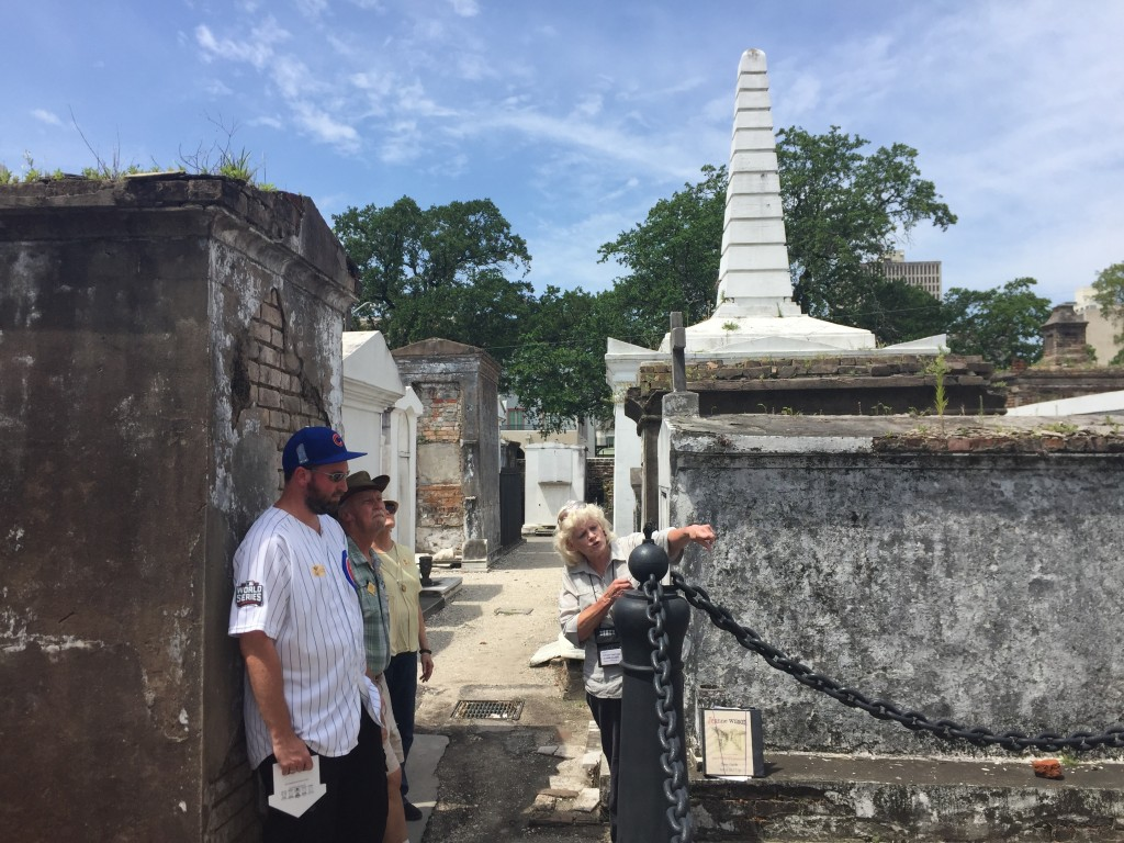 This June 3, 2018 photo shows tour guide Jeanne Wilson of Save Our Cemeteries with a group of visitors at St. Louis Cemetery No. 1 in New Orleans. Tou...