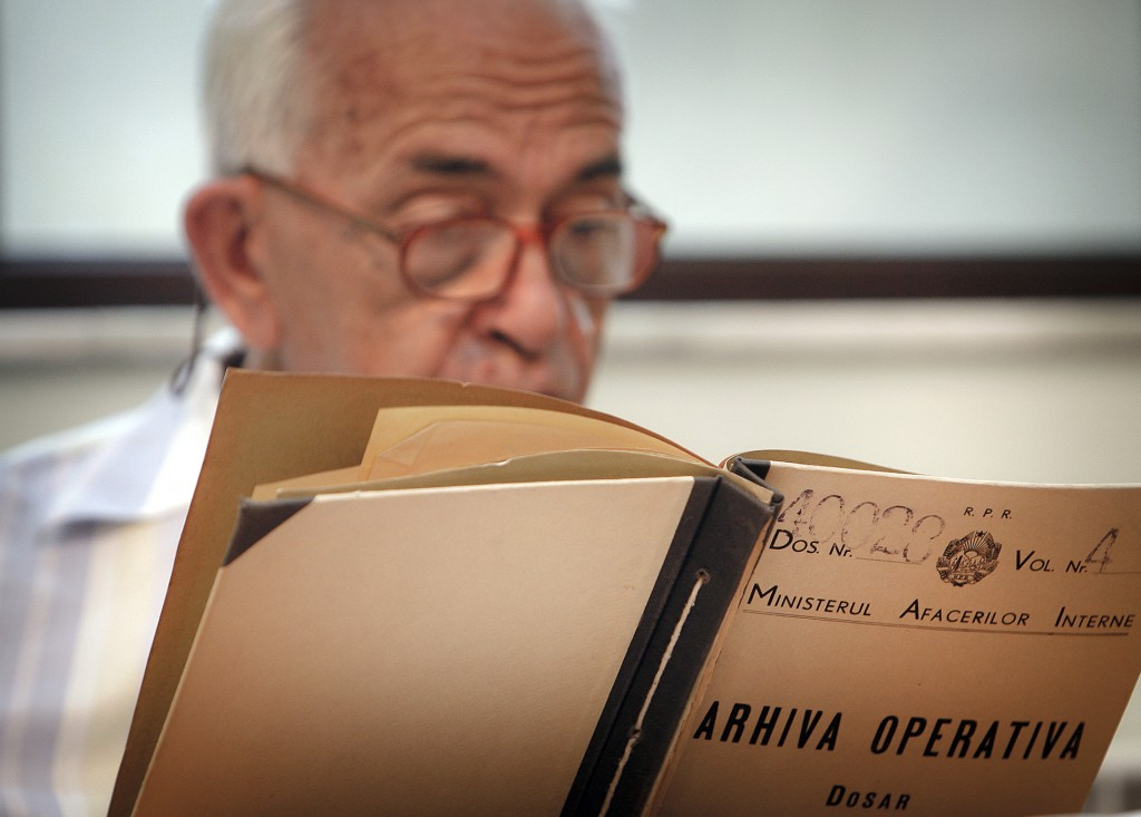 FILE - In this July 29, 2009, file photo, a man who refused to be identified by name reads a communist era secret police file at the headquarters of t...