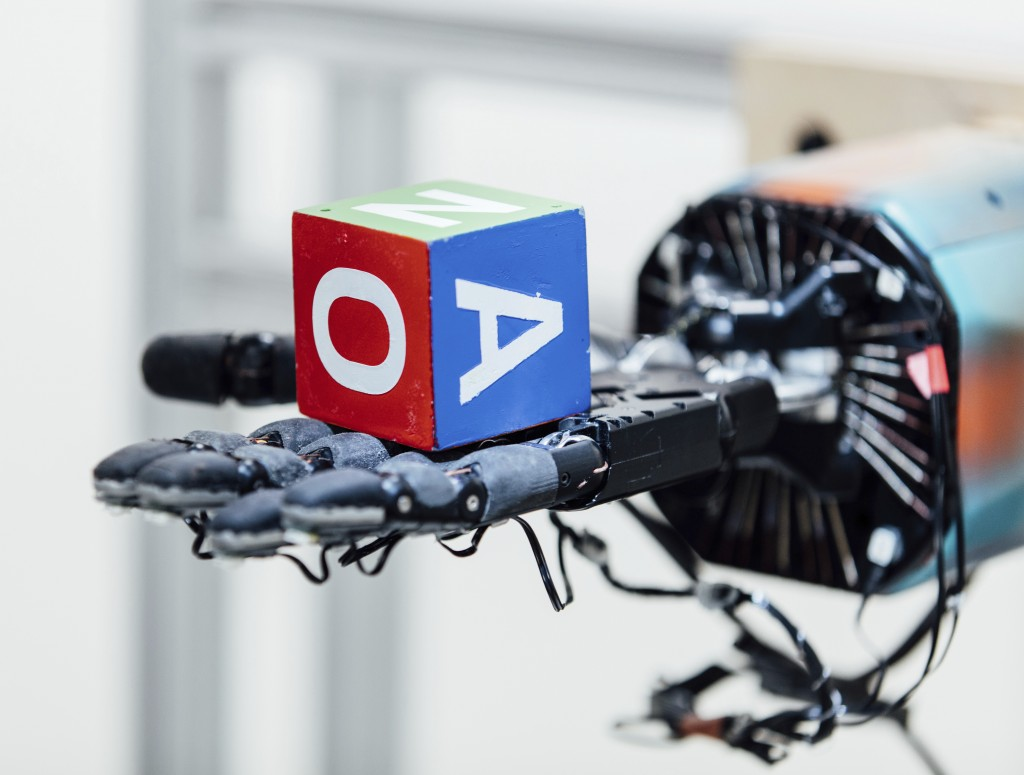This undated photo provided by OpenAI shows a robotic hand holding a cube at the company's research lab in San Francisco. The hand, called Dactyl, has...