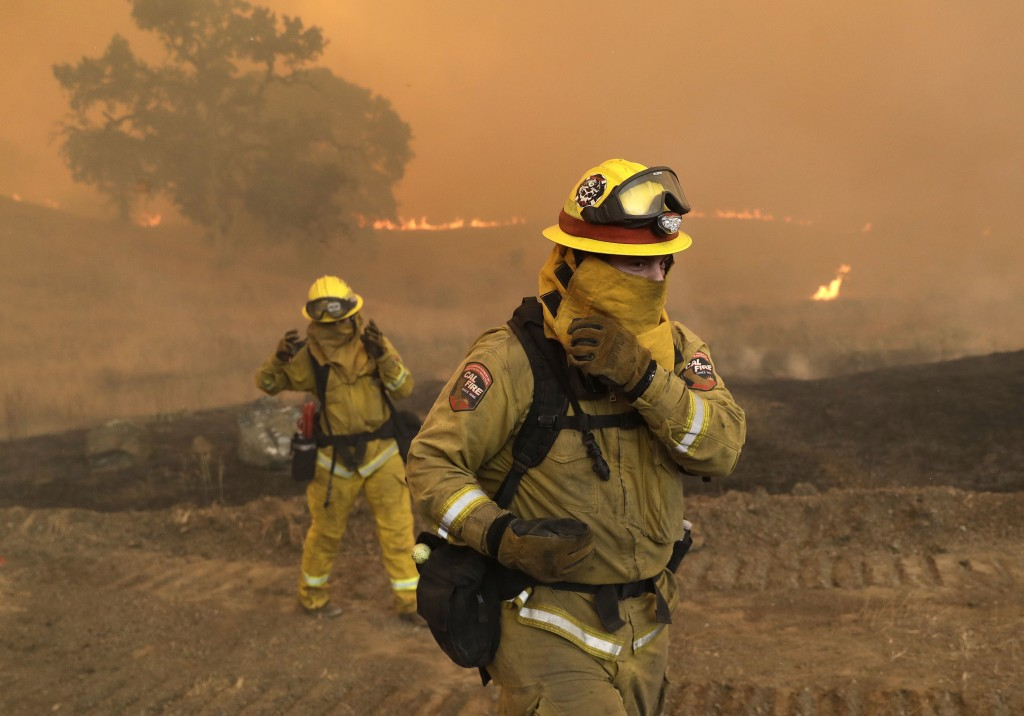 Firefighters with Cal Fire Mendocino Unit cover themselves from smoke and ash created by an advancing wildfire Monday, July 30, 2018, in Lakeport, Cal...