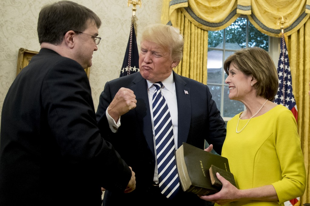 President Donald Trump, pumps his fist as Robert Wilkie, left, accompanied by his wife Julia, right, is sworn in as Secretary of the Department of Vet...