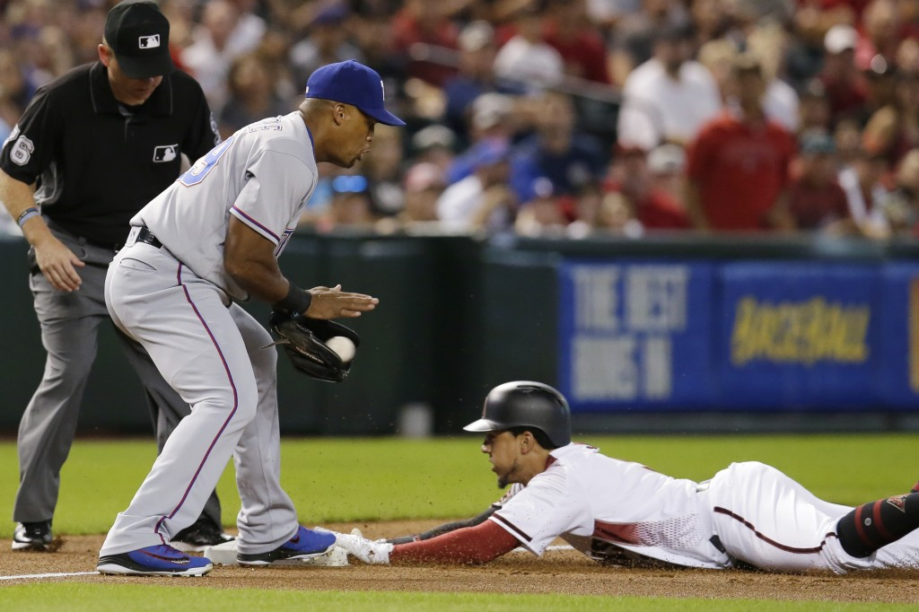 Arizona Diamondbacks Jon Jay, right, dives into third base after hitting a lead off triple in front of Texas Rangers third baseman Adrian Beltre in th...