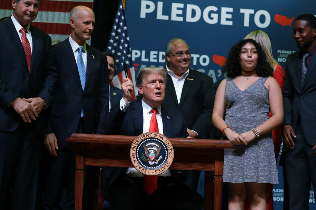 "President Donald Trump gestures as he signs the ""Strengthening Career and Technical Education for the 21st Century Act,"" at Tampa Bay Technical High S..."