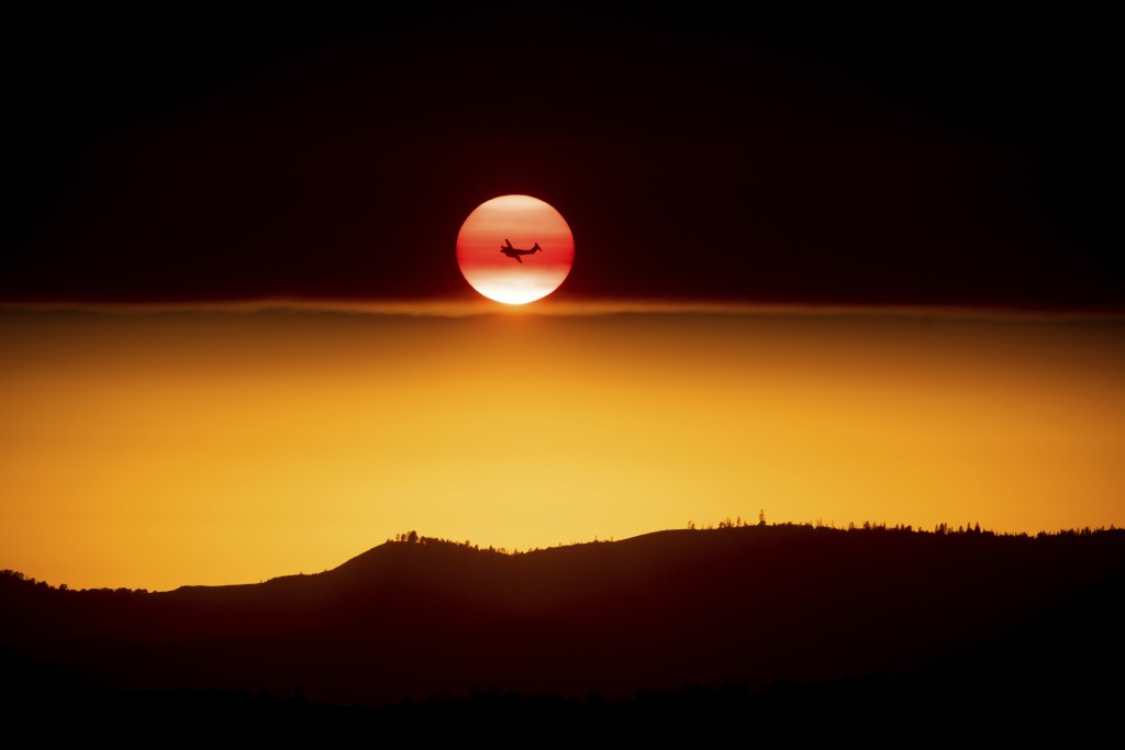 A plane battling the Ferguson Fire passes the setting sun in unincorporated Mariposa County Calif., near Yosemite National Park on Sunday, July 15, 20...