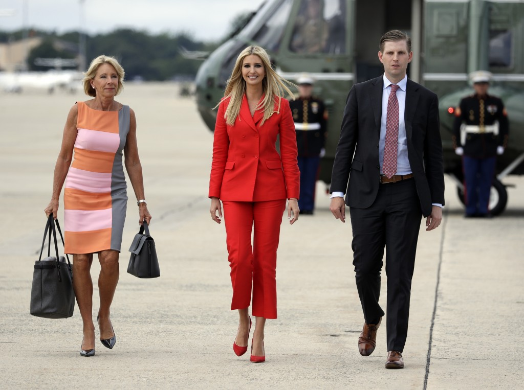 Ivanka Trump, the daughter of President Donald Trump, center, walks with Education Secretary Betsy DeVos, left, and Eric Trump, son of President Donal...