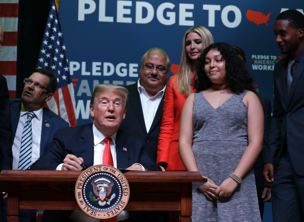 "President Donald Trump signs the ""Strengthening Career and Technical Education for the 21st Century Act,"" at Tampa Bay Technical High School, Tuesday,..."