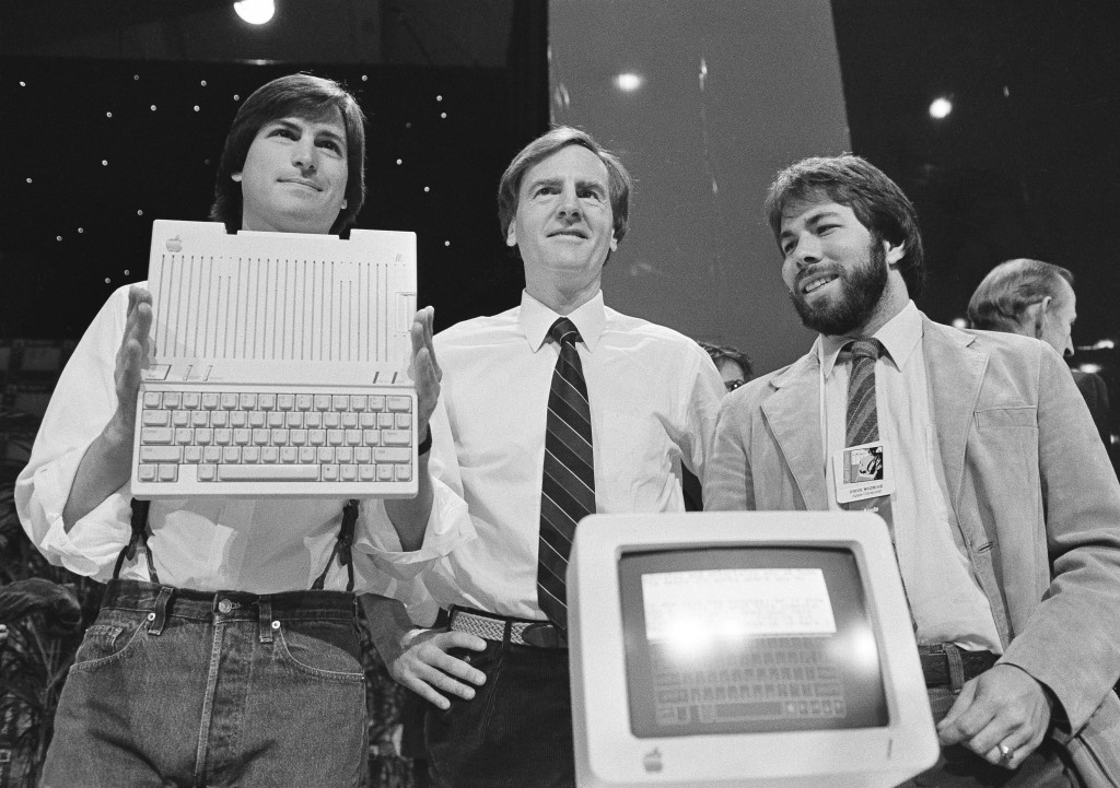 FILE - In this April 24, 1984 file photo, Steve Jobs, left, chairman of Apple Computers, John Sculley, center, president and CEO, and Steve Wozniak, c...