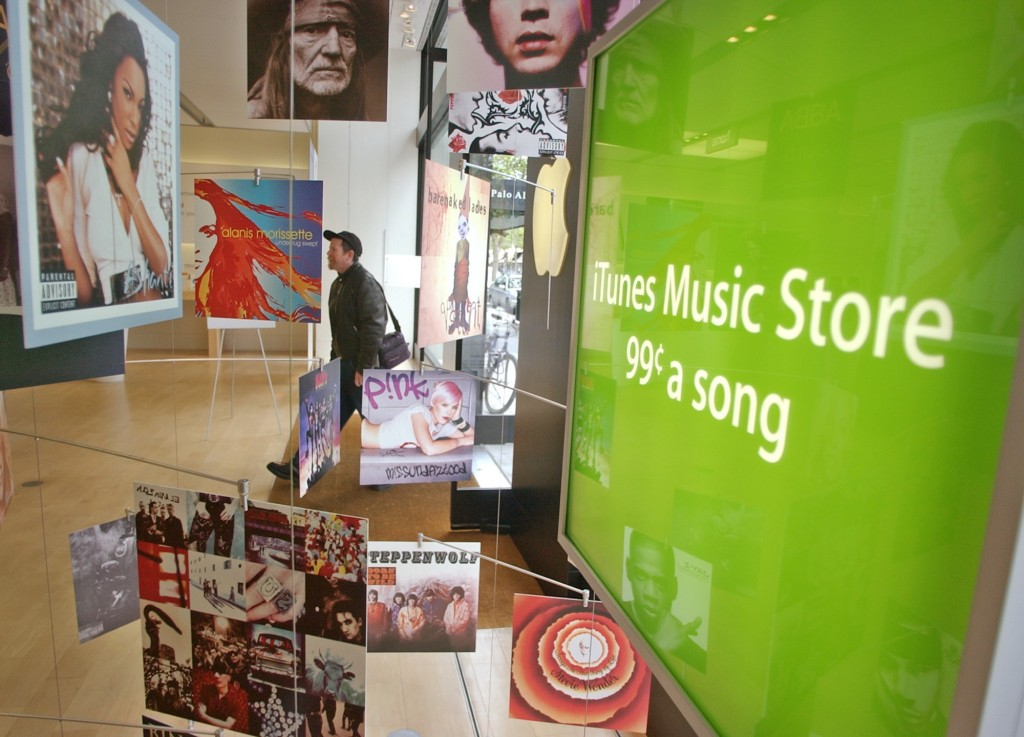 FILE - In this May 6, 2003 file photo, Apple Computer customer walks into an Apple store in Palo Alto, Calif., passing a display of music albums for A...