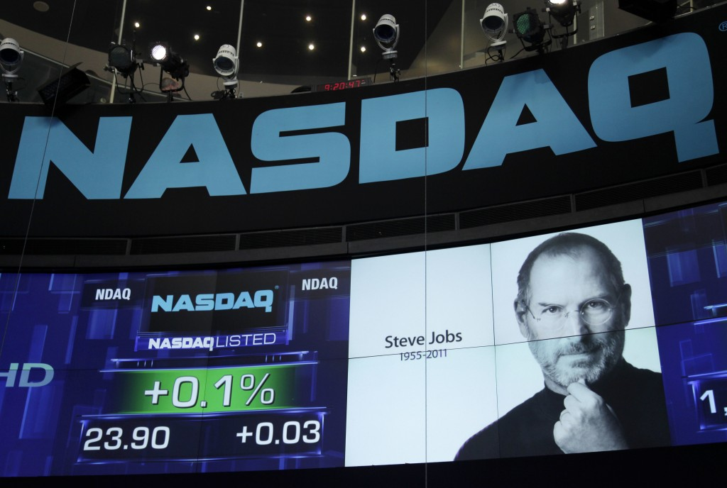 FILE - In this Oct. 6, 2011 file photo, a photo of Apple co-founder Steve Jobs is displayed as a tribute at Nasdaq in New York. Jobs died Wednesday at...