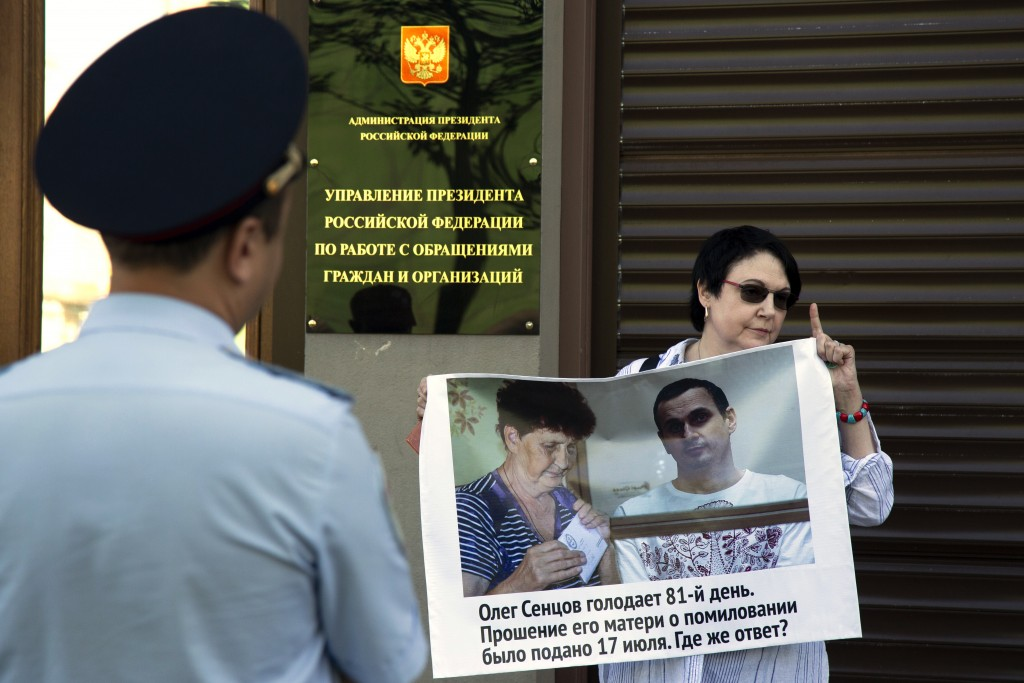 "A woman holds a poster reading ""Oleg Sentsov is on hunger strike for the 81st day. His mother lodged a petition for pardon on July 17, 2018, Where's t"