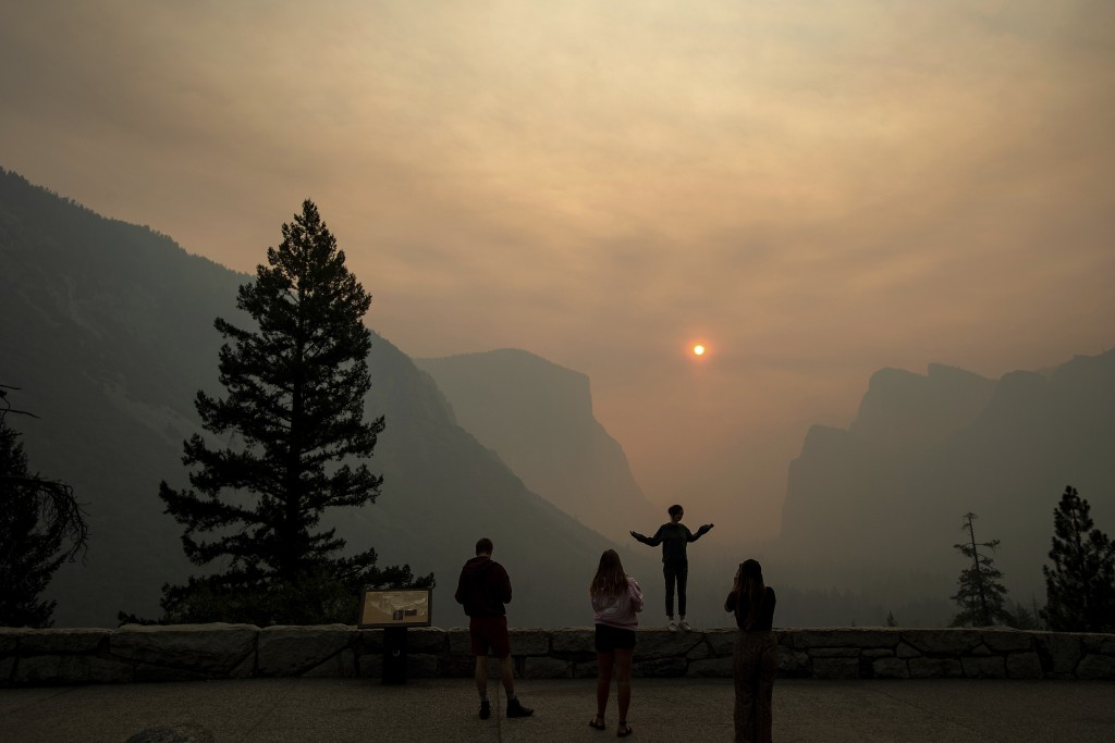 FILE - In this July 25, 2018 file photo, Hannah Whyatt poses for a friend's photo as smoke from the Ferguson fire fills Yosemite Valley in Yosemite Na...