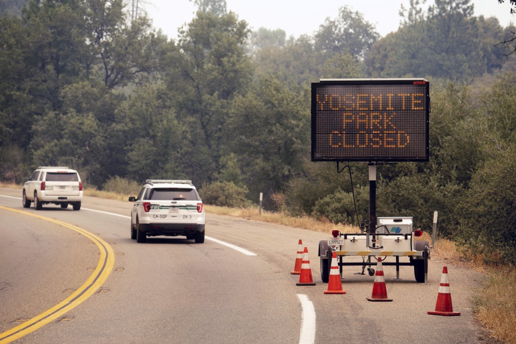 FILE - In this July 25, 2018 file photo, a sign on Highway 41 announces the closure of Yosemite National Park near Oakhurst, Calif. Yosemite National ...