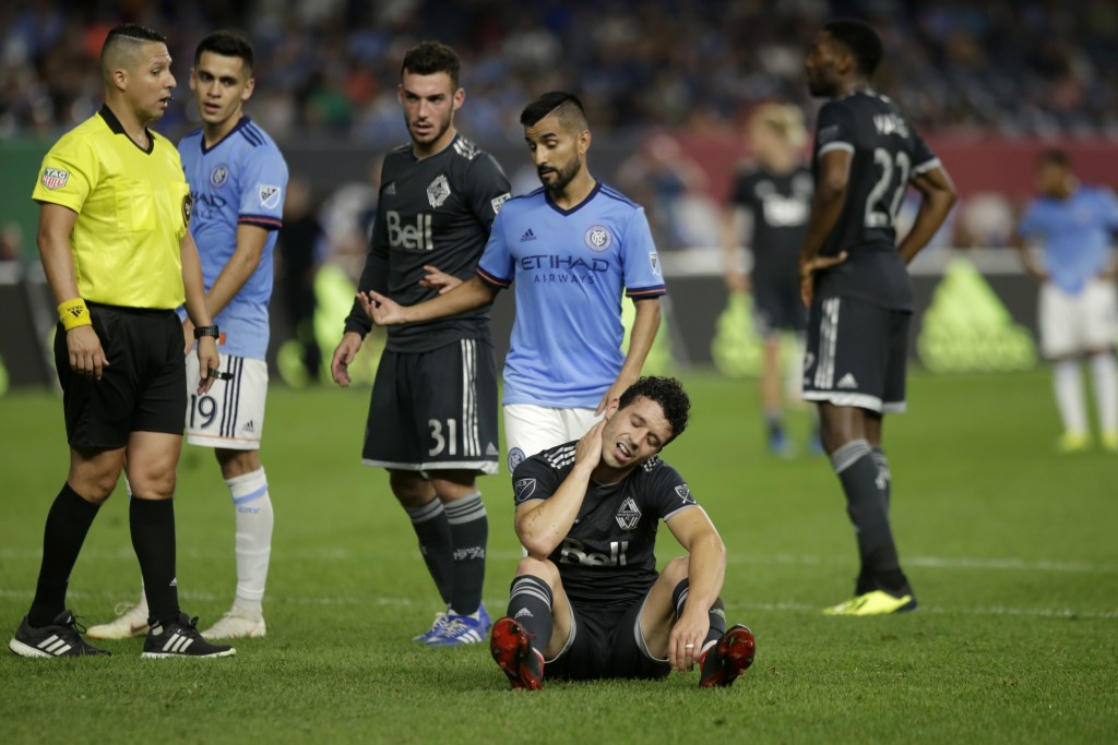 New York City FC's Maximiliano Moralez gestures as Vancouver Whitecaps' Felipe Martins sits on the pitch during the second half of an MLS soccer match...
