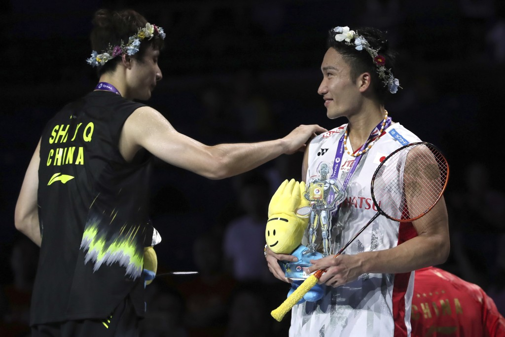 Kento Momota of Japan, right, talks with Shi Yuqi of China on the podium after beating Shi in their men's badminton championship match at the BWF Worl...