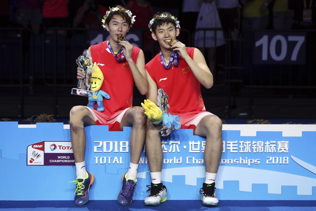 Li Junhui, left, and Liu Yuchen of China sit at the podium with their medals after beating Takeshi Kamura and Keigo Sonoda of Japan in their men's dou...