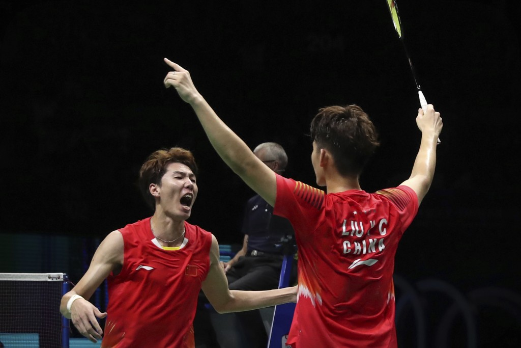 Li Junhui, left, and Liu Yuchen of China react after beating Takeshi Kamura and Keigo Sonoda of Japan in their men's doubles badminton championship ma...