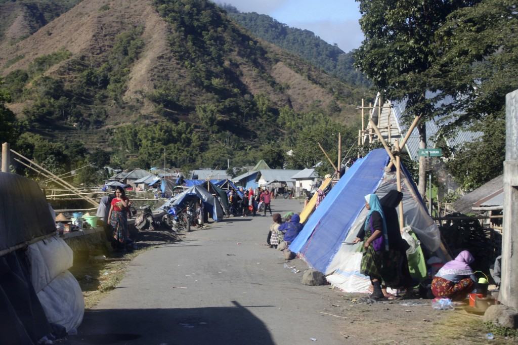 People affected by an earthquake take shelter in tents erected on the side of a road in Sembalun on Lombok Island, Indonesia, Monday, Aug. 6, 2018. Th