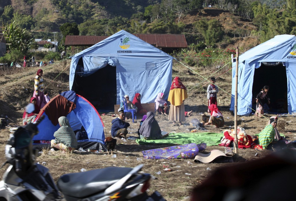People affected by an earthquake sit outside their makeshift tents in Sembalun, on Lombok Island, Indonesia, Monday, Aug. 6, 2018. The powerful earthq