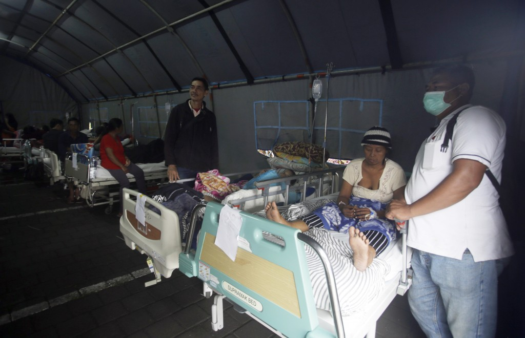 Patients are evacuated to a tent outside a hospital, following an earthquake in Bali, Indonesia, Monday, Aug. 6, 2018. A powerful earthquake struck th