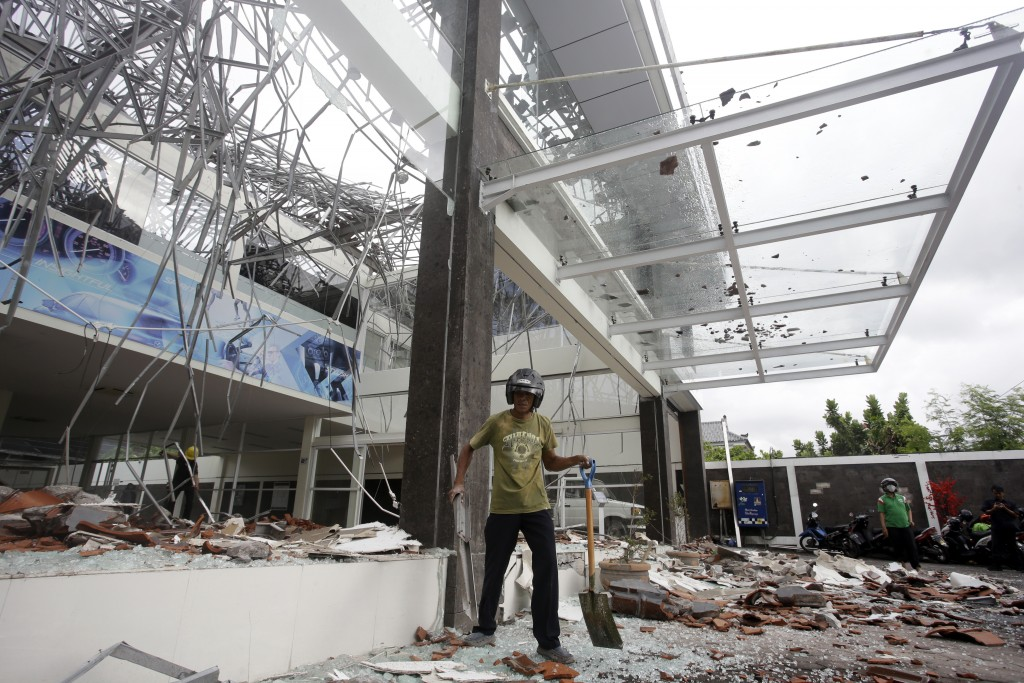 A man cleans up at a building damaged by an earthquake in Bali, Indonesia, Monday, Aug. 6, 2018. A powerful earthquake struck the Indonesian tourist i...