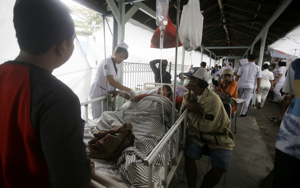 Patients are evacuated outside a hospital, following an earthquake in Bali, Indonesia, Monday, Aug. 6, 2018. A powerful earthquake struck the Indonesi