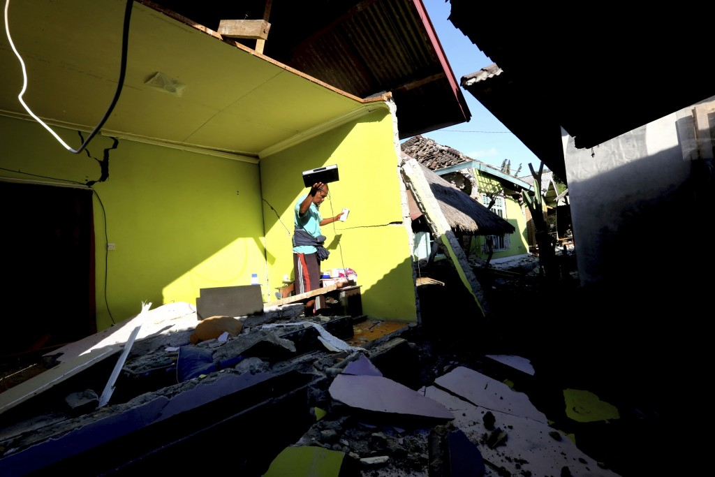 In this Monday, Aug. 6, 2018, file photo, usable items are salvaged from a home destroyed in an earthquake in North Lombok, Indonesia. The powerful ea