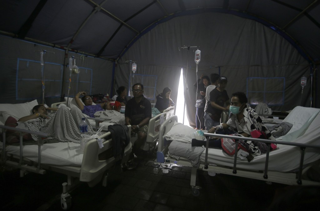 Patients are evacuated to a tent outside a hospital, following an earthquake in Bali, Indonesia, Monday, Aug. 6, 2018. A powerful earthquake struck th...