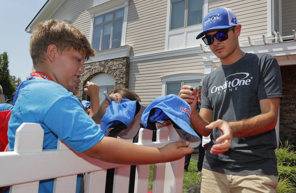 Kyle Larson signs autographs before a NASCAR Cup series auto race, Sunday, Aug. 5, 2018, in Watkins Glen, N.Y. (AP Photo/Julie Jacobson)