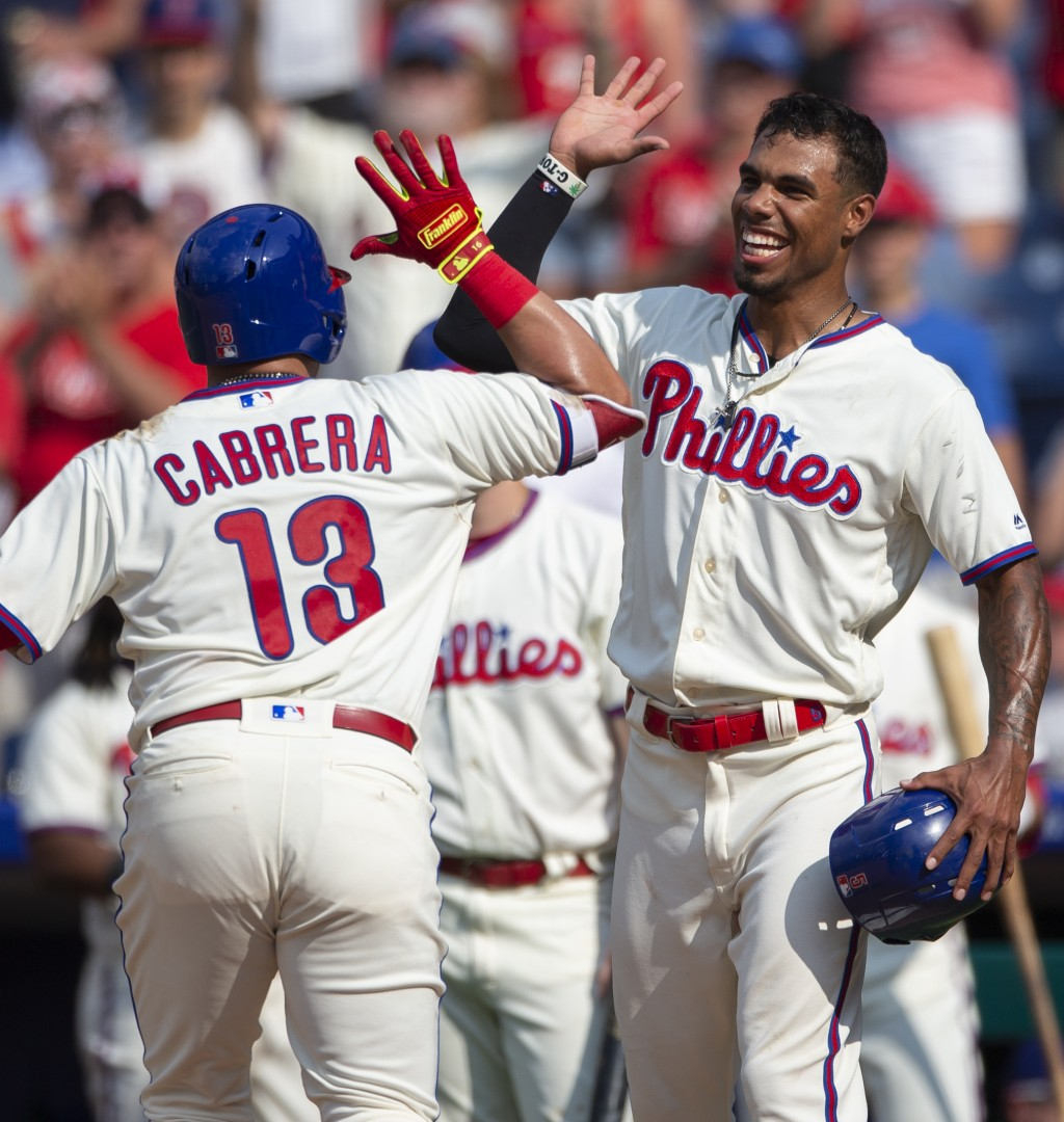 Philadelphia Phillies' Asdrubal Cabrera (13) high-fives Nick Williams after hitting a two-run home run in the eighth inning of a baseball game against...