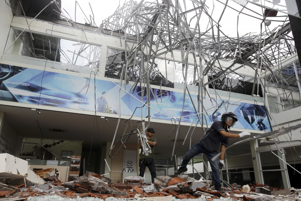 In this Monday, Aug. 6, 2018, file photo, workers remove the debris at a building damaged by an earthquake in Bali, Indonesia. A powerful earthquake s...