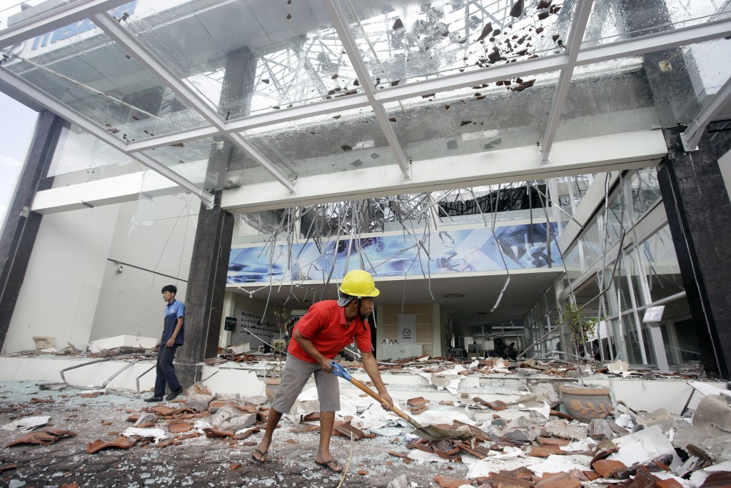 In this Monday, Aug. 6, 2018, photo, workers clean up debris at a building damaged by an earthquake in Bali, Indonesia. (AP Photo/Firdia Lisnawati)