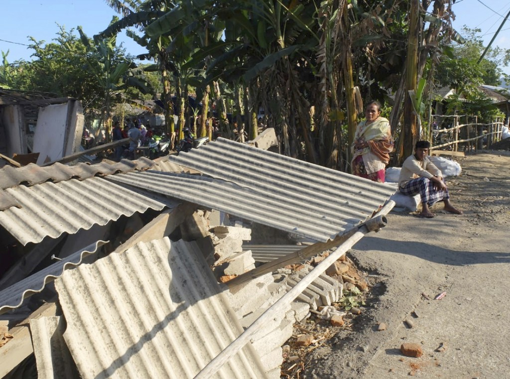 Residents look at a damaged building following an earthquake in North Lombok, Indonesia, Monday, Aug. 6, 2018. A powerful earthquake struck the Indone...