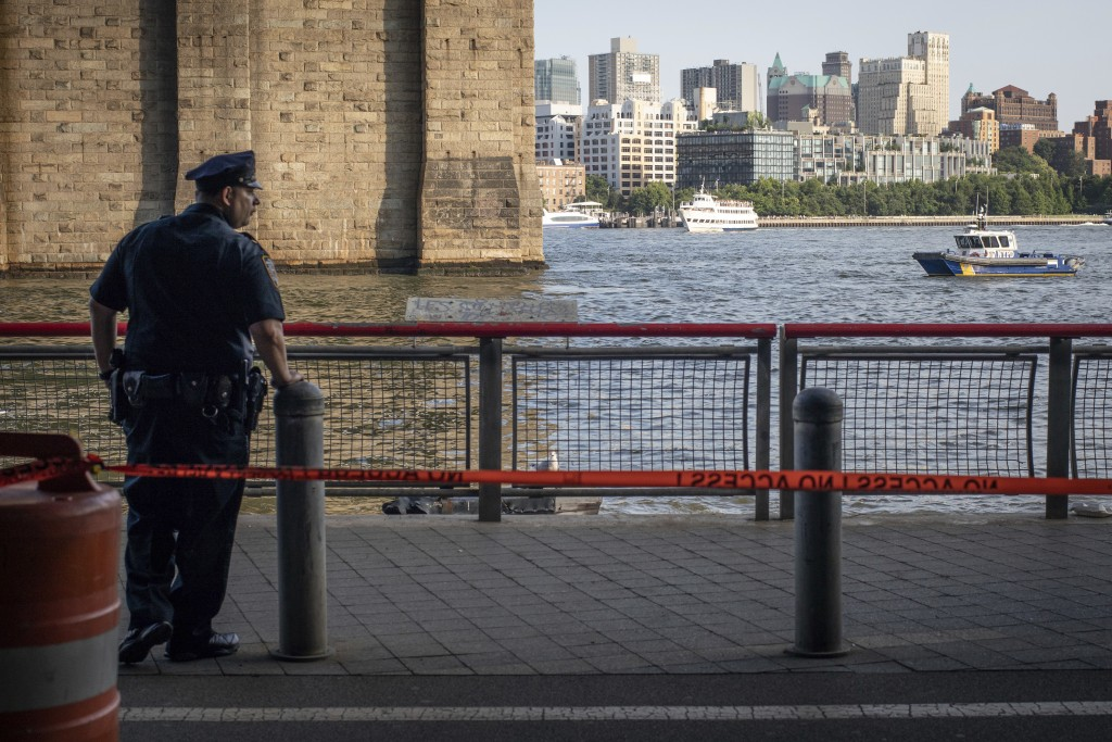 A New York Police Department officer stands guard as authorities investigate the death of a baby boy who was found floating in the water near the Broo