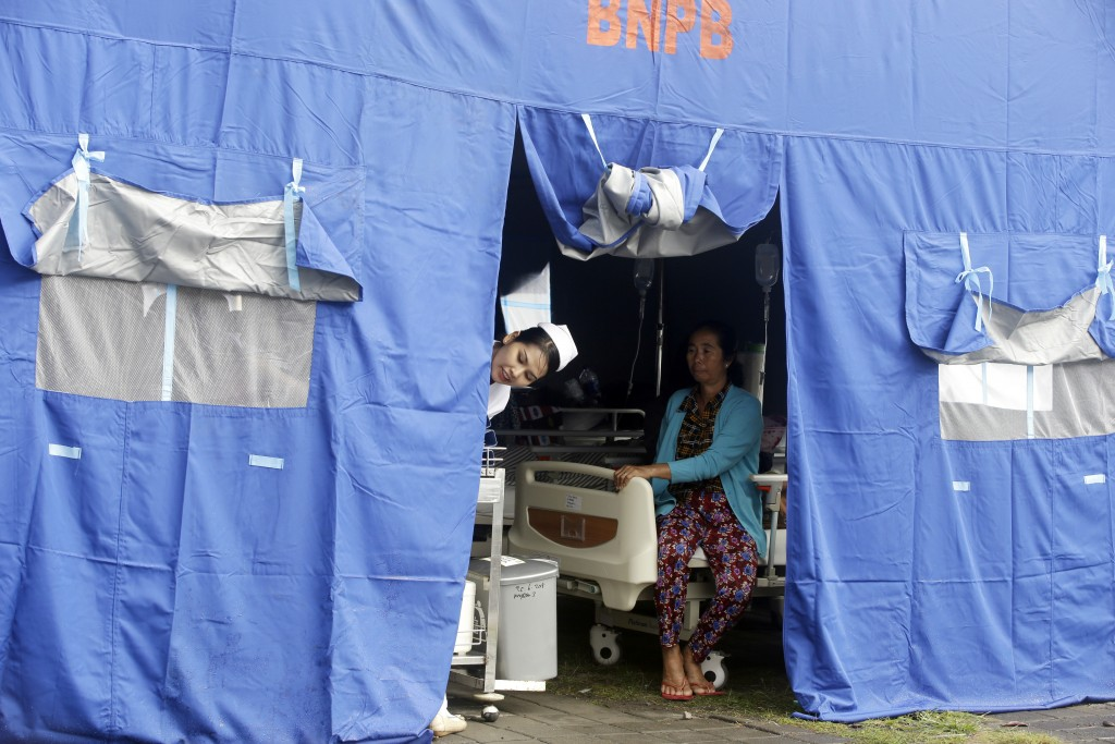 A nurse looks out of a tent where patients were evacuated from a hospital, following an earthquake in Bali, Indonesia, Monday, Aug. 6, 2018. A powerfu