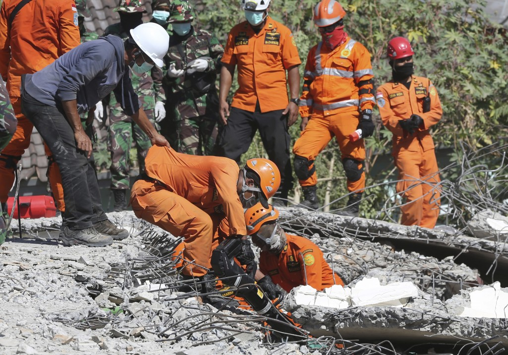 In this Tuesday, Aug. 7, 2018, photo, rescuers carry the body of an earthquake victim recovered from the collapsed Jabal Nur mosque in North Lombok, I...