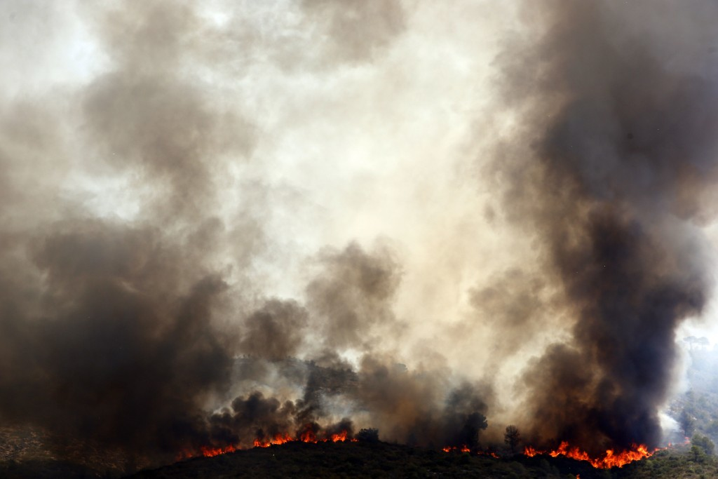 Spanish firefighters try to extinguish a wildfire in Pinet village, near Valencia Tuesday, Aug. 7, 2018. Spanish firefighters are still working to bri