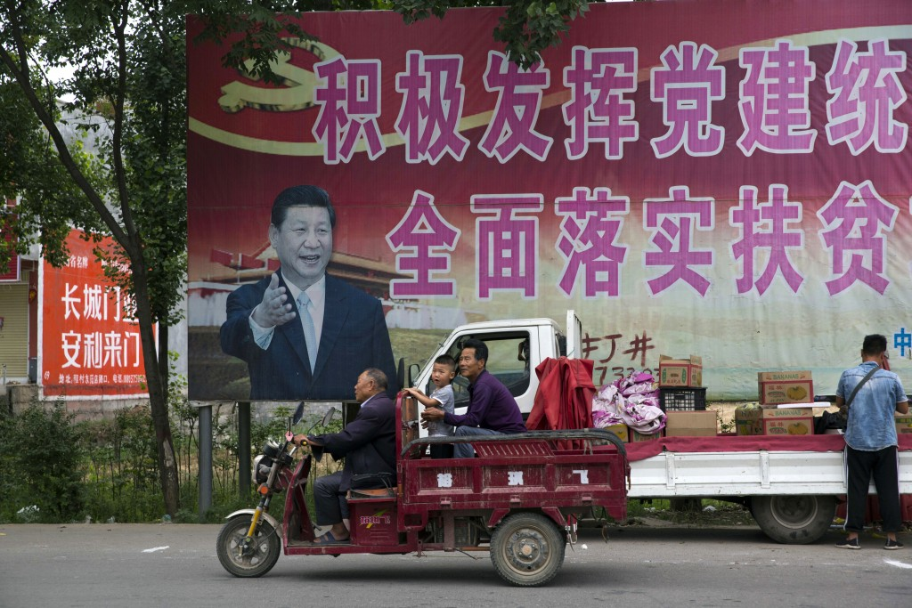 "In this photo taken Saturday, June 2, 2018, residents past by a poster of Chinese President Xi Jinping and part of the slogans which reads ""Actively p"