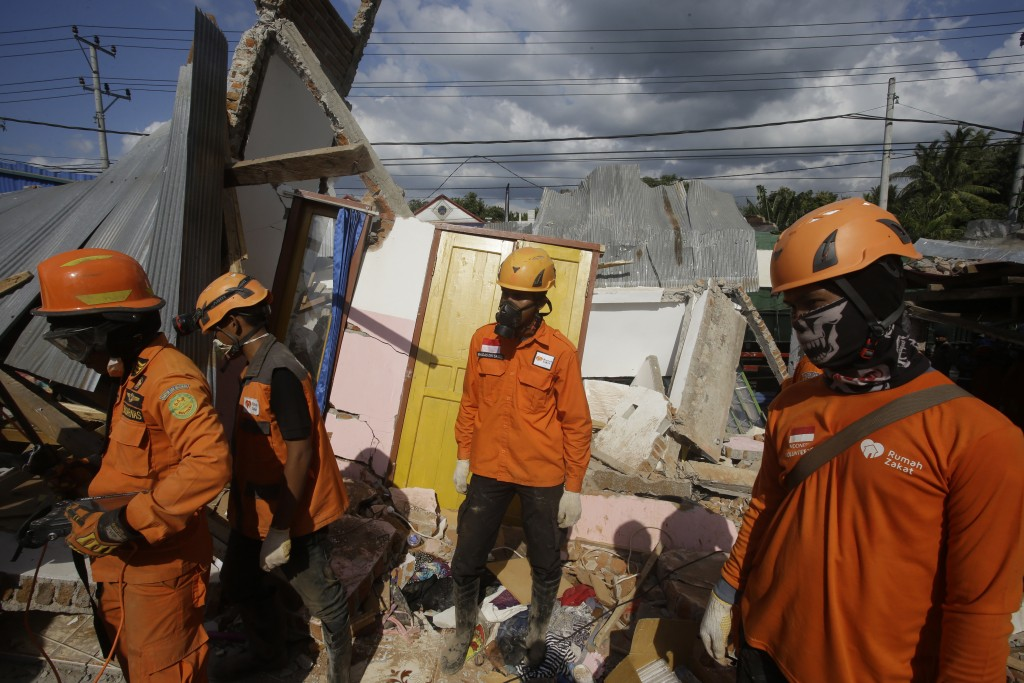 Emergency teams continue to search for victims in an earthquake-damaged house in Tanjung, Lombok, Indonesia, Tuesday, Aug. 7, 2018. Thousand left home...