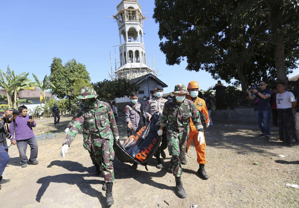 In this Tuesday, Aug. 7, 2018, photo, rescuers carry a body of an earthquake victim recovered from the collapsed Jabal Nur Mosque in North Lombok, Ind...