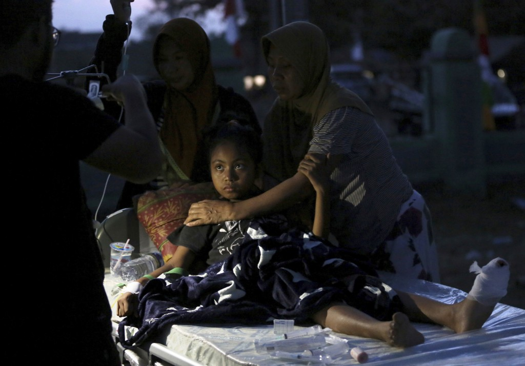 In this Tuesday, Aug. 7, 2018, photo, a  doctor examines a child injured in the earthquake at a makeshift hospital in Tanjung, North Lombok, Indonesia...