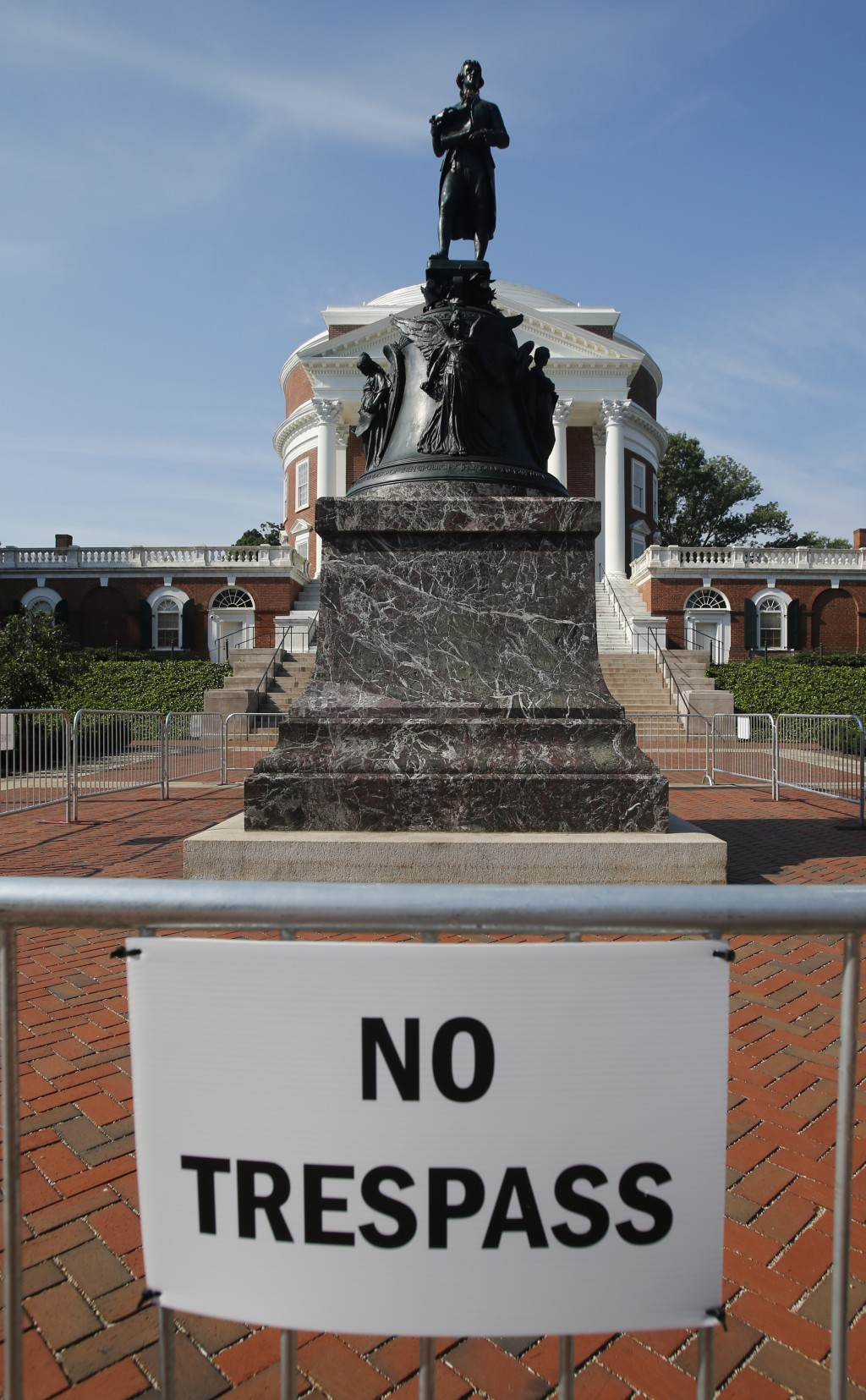 In this Monday, Aug. 6, 2018 photo, a statue of Thomas Jefferson is surrounded by fencing and a No Trespassing sign in front of the rotunda on the cam