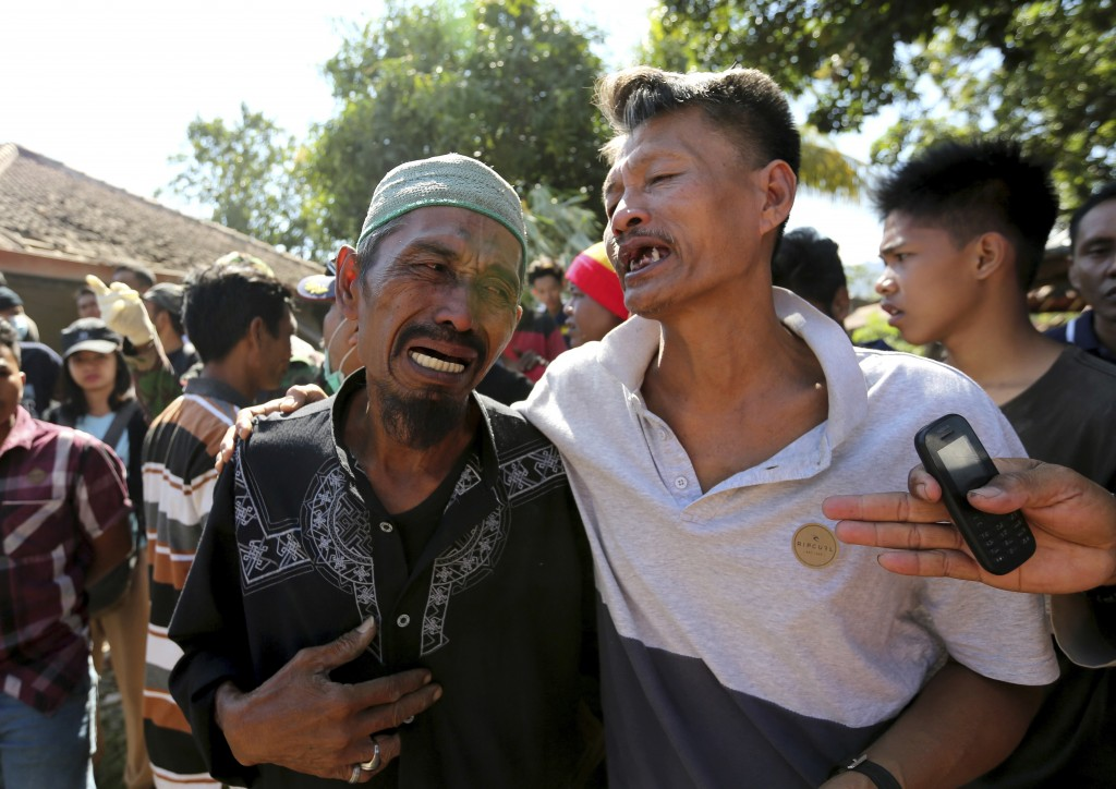 In this Tuesday, Aug. 7, 2018, photo relatives react as rescue teams recover the bodies of victims killed in an earthquake in North Lombok, Indonesia,...
