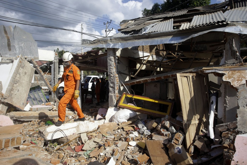 Emergency rescue team members continue to search for victims in the quake-damaged village in Tanjung, Lombok, Indonesia, Tuesday, Aug. 7, 2018. Thousa...