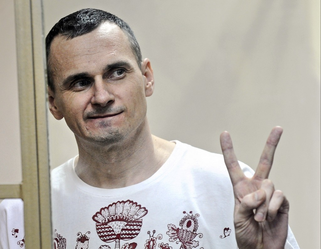 FILE - In this Tuesday, Aug. 25, 2015 file photo, Oleg Sentsov gestures as the verdict is delivered, as he stands behind bars at a court in Rostov-on-...
