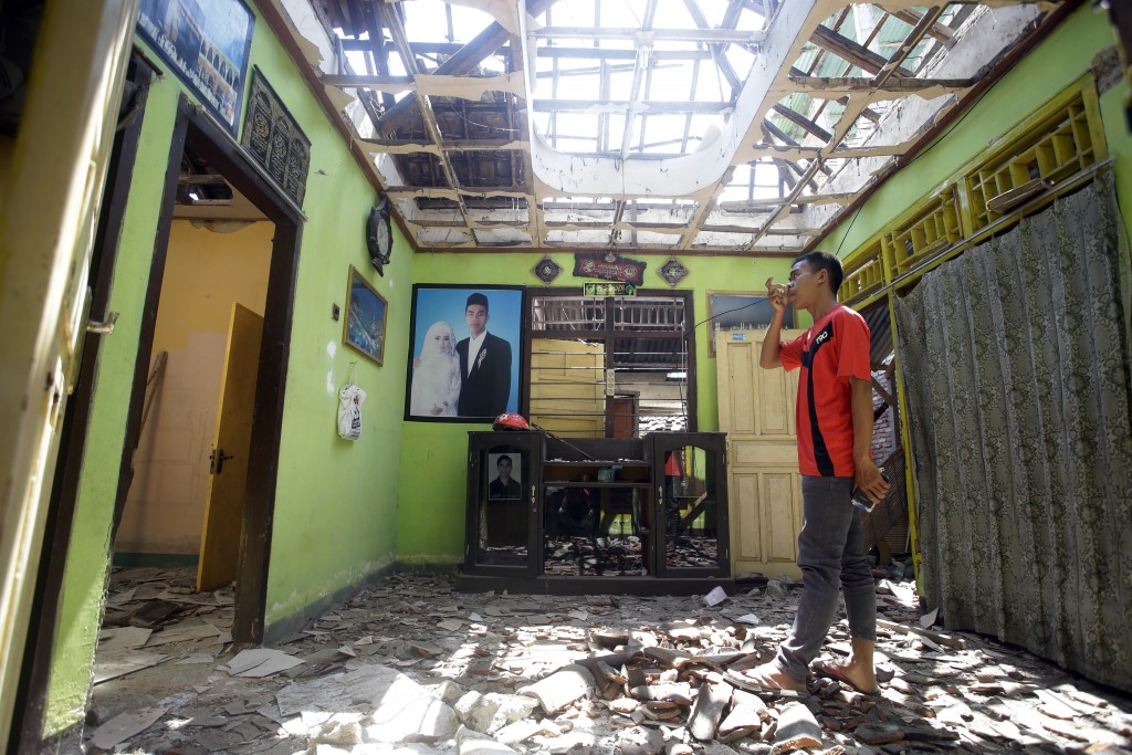 A villager visits his damaged house in the Kekait village affected by Sunday's earthquake in North Lombok, Indonesia, Wednesday, Aug. 8, 2018. Aid has